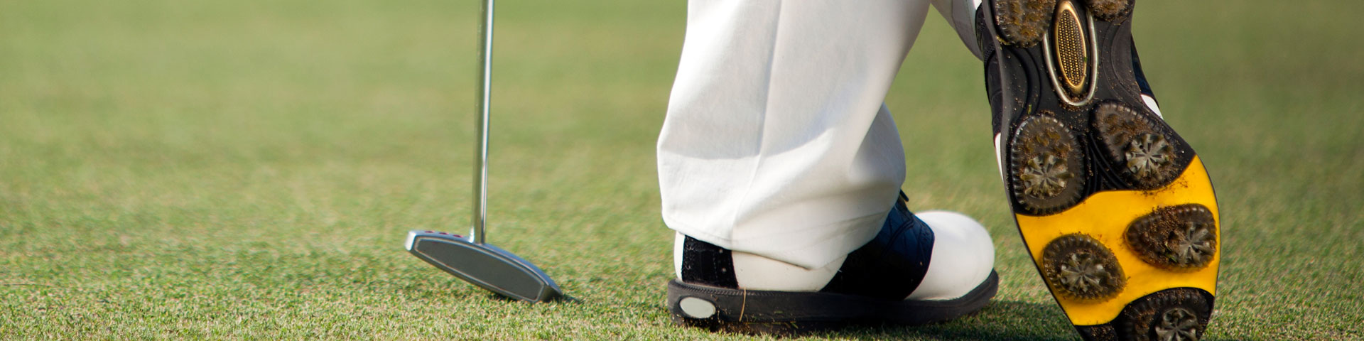 A person's golf shoes accompanied by a club